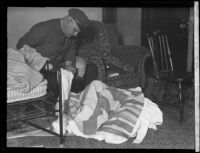 Motorcycle officer Howard J. Garner examining linens found in the apartment of William Edward Hickman murderer of Marion Parker, 1927