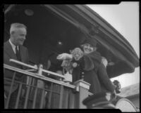 President Herbert Hoover standing on the back of a railroad car with first Lady Lou Henry Roosevelt holding a lion cub, El Monte, 1932
