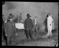 Rescue workers carry the covered remains of a victim of the fire at the Hope Development School for mentally disabled girls in Playa del Rey, Los Angeles, 1924