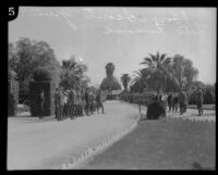 Boy Scouts stand at attention at the gates of the Hollywood Cemetery for the funeral procession for Arthur Letts, Los Angeles, 1923