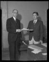 Carl S. Kegley, attorney, receives a document from Municipal Judge Wilbur C. Curtis, Los Angeles, circa 1933