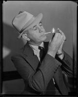 Jack Kearns, boxing manager, lighting a cigarette