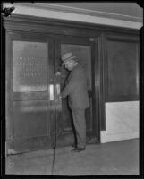 Asa Keyes, district attorney of Los Angeles County, at the closed door of the District Attorney office, 1923-1928