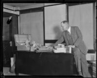 Asa Keyes, district attorney of Los Angeles County, with a suitcase and belongings, Los Angeles, 1923-1928
