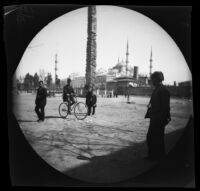 Thomas Allen riding a bicycle at the Hippodrome of Constantinople (Sultanahmet Meydanı), and in front of the  Sultanahmet Camii, Istanbul, 1891