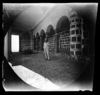 E. T. Platt standing in the portico of the chapel containing the tomb of Ali's sons, Tabriz vicinity, Iran, 1891