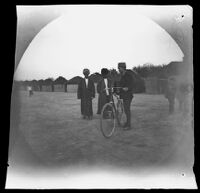 "Thomas Allen showing his bicycle to two men at a Turkmen encampment at ""Kashee,"" Ashkhabad vicinity, Turkmenistan, 1891"