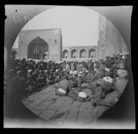 Religious teachers performing a sacred drama in Registan Square with Tilakari Mosque in the background, Samarqand, Uzbekistan, 1891