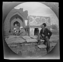 Thomas Allen seated in front of a 14th-15th century Qur'an stand in the courtyard of Bibi-Khanym Mosque, Samarqand, Uzbekistan, 1891