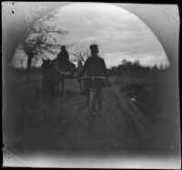 Thomas Allen on his bicycle passing a cart on the road to Bukhoro, Uzbekistan, 1891
