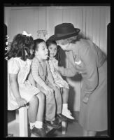 Nurse Cleo E. Thompson examining children, Santa Barbara, 1947