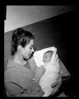 Dana Wynter holds her newborn son, Mark Bautzer, Los Angeles, 1960
