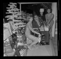 Veteran Allan Jarabin, with Shirley Jones, Dana Wynter and Lydia Lane, receives a present at Lydia Lane's annual Christmas party honoring military veterans, [Los Angeles?], 1963