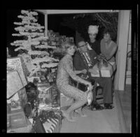 Veteran Allan Jarabin, with Shirley Jones, Dana Wynter and Lydia Lane, receives a present at Lydia Lane's annual Christmas party honoring military veterans, [Los Angeles?], 1963