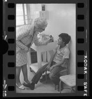 School nurse Nina Melching takes the temperature of Jesse Orona, East Los Agneles, 1972