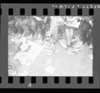 Delegates at the Democratic National Convention sit over posters for candidates strewn on the floor, Los Angeles, 1960
