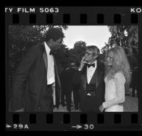 "Earvin ""Magic"" Johson speaking with Bo Hopkins and an unidentified women at a City of Hope party at Pickfair honoring Jerry Buss, Beverly Hills, 1981"