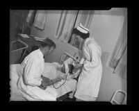 Attendant Clement and Nurse Leah Lewis inject a patient with insulin to induce coma as part of a treatment for insanity at the Camarillo State Hospital, 1940