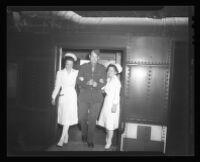 Corporal William W. LeSueur, Lieutenant Anne Wojcik, and Lieutenant Thekla Lennon exiting a hospital train, Van Nuys, 1944