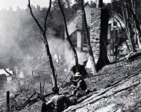 Two men survey the charred remains of the Mt. Lowe Tavern fire, Mt. Lowe, 1936