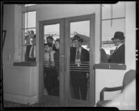 Spectators looking into Bank of America after robbery, Los Angeles, 1936