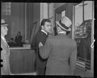 Edward Hill, bank guard, turns to talk to a man after the bank was robbed, Los Angeles, 1936
