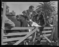 Man looks through a registration book at the annual Iowa Picnic in Lincoln Park, Los Angeles, 1936