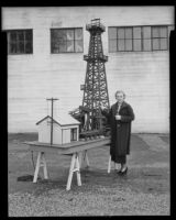 Whittier College co-ed Alma Furman stands beside Elmer Calkins' model oil derrick, Whittier, 1936