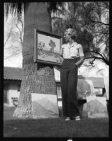 Doris Dalzell admires a painting at an outdoor art gallery, Palm Springs, 1936
