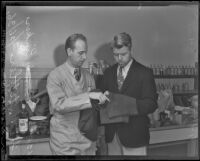 Murder suspect Fred Stettler holds his stained pants in front of chemist Ray Pinker, Los Angeles, 1936