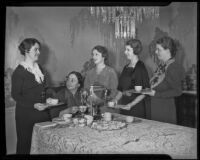 Five members of the Women's Auxiliary of the California Babies Hospital surround a dining room table, 1936