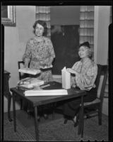 Daughters of the American Revolution members Mrs. George Craig and Nelle Holbrook wrap presents, 1936