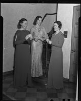 Helen Mary Healy, Gwendolyn Dorsey, and Dorothy Merrill pose by a staircase holding slips of paper, Beverly Hills, 1936