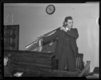 Leroy Saunderson stands in the witness box with a shotgun, Los Angeles, 1935