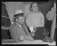 "Detective Lieutenant Frank Harper examine's Lyndon ""Red"" Foster's injured hand, Los Angeles, 1935"