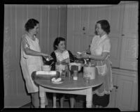 Cecilia La Sage, Anita Arnold, and Adelaide Wagner, members of the Catholic Women's Club Juniors bake for Christmas party, 1935
