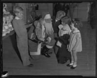 Santa Claus offers a doll to young girls, Los Angeles, 1935