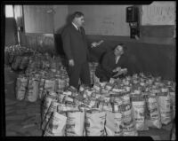 Captain Eddie Slaughter and Lieutenant G. E. Fisher prepare food donations for Christmas, Los Angeles, 1935