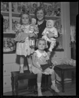 Harriet McCabe and 3-year-old girls Sally Anne Davis and Nancy Lee Davis with Mrs. McCabe's doll collection, Pasadena, 1935