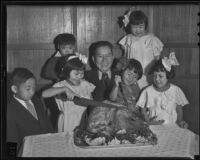 Cafe owner Tabin Kato seated before a turkey dinner with 6 children, Los Angeles, 1920-1936