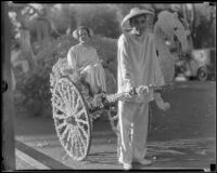 "Girl in a rickshaw drawn by a boy next to the ""Chinese Empress"" float in the Tournament of Roses Parade, Pasadena, 1936"