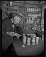 Gardener Henry O'Melveny with containers of seeds, Los Angeles, 1936
