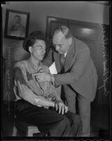 Detective Captain Bert Wallis inspects a blood stain on murder suspect James Fagan Culver, Los Angeles, 1936
