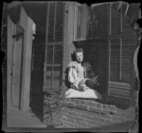 Prostitute sits in the window of a crib on Alameda Street, Los Angeles, 1896
