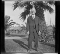 Abraham Whitaker stands in Alhambra Park in front of a large palm tree, Alhambra, about 1930