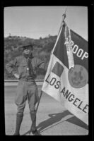 H. H. West Jr. wears a Boy Scouts uniform and holds a flag in Griffith Park, Los Angeles, about 1932