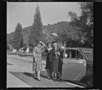 Mertie West holds open the door of a car while her step-daughter, Elizabeth Siemsen and granddaughter, Dorothea Siemsen stand behind her, Glendale, 1942
