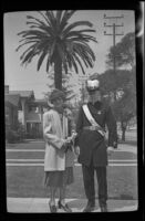 Mertie West and H. H. West, in Knights Templar uniform, pose with a large palm tree in the background, Los Angeles, 1939