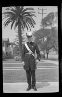 H. H. West poses wearing his Knights Templar uniform with a large palm tree in the background, Los Angeles, 1939