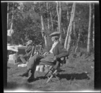 Abraham Whitaker sits on a chair while H. H. West Jr. sits at a table while camping at Convict Lake, Mammoth Lakes vicinity, 1929
